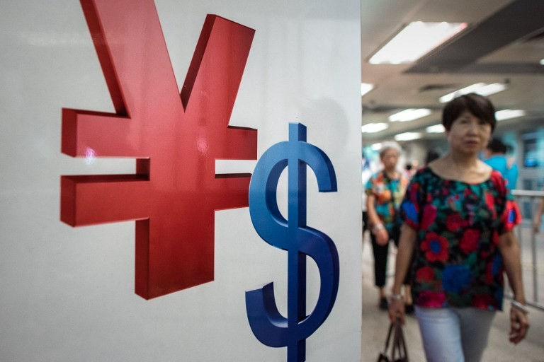 A woman walks past a yuan (L) and a US dollar (R) currency sign in Hong Kong on August 13, 2015.   China cut the reference rate for its currency for the third straight day on August 13, authorities said, after their surprise devaluation of the yuan this week unsettled global financial markets. AFP PHOTO / Philippe Lopez